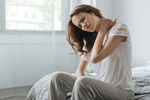 Neck inflammation. Moody unhappy young woman sitting on the bed and holding her neck while having an inflammation there